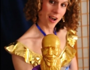 trans-woman in shiny dress and pantyhose stuffs Obama dildo in her asspussy.